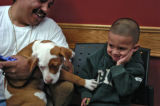 Juan Flores (cq) holds his dog Pancho with his 2 year old son Anthony Flores in the office of...