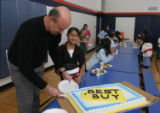Best Buy district manager Jeff Fogelman serves cake to Irma Guzman, Monday, Jan. 16 2006, at the...