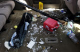 Glass, trash and snow litter the floor of a wrecked van that sits in a lot at Oasis Service in...