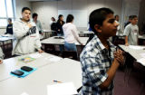 "Omar Martinez, cq, (right) places his hand over his heart as the class recites the ""Pledge of..."