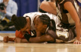 Adrianne Ross, of TCU, left, and Dominique Sisk, right, of Wyoming fight for a loose ball in the...