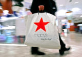 A shopper walks through the cosmetics department with a shopping bag emblazoned with the red star...