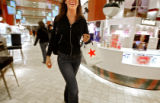 A female shopper carries a small bag bearing the red star symbol of Macy's as she strolls through...