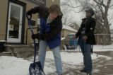 Patty Moore, left, gives Sharita Richmond a snow shoveling lesson in front of Moore's store, Le...