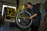 Dirk Boswell (cq) works on the front wheel of a Board Walker, different type of Pedicab,Tuesday...