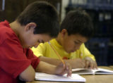 (DENVER, Colo., July 12, 2004)  Osvaldo Navarro,10 concentrates on his writing assignment  at the...