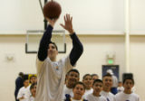 Denver Nugget Eduardo Najera shoots three-pointers for a group of kids at a basketball clinic for...