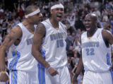 Denver Nuggets players Kenyon Martin, left, and Ruben Patterson, right, cheer on teammate Carmelo...