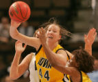 Iowa's Megan Skouby, middle, looks to pass the ball in the first half of play in the first round...