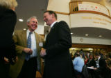Dick Notebaert, CEO of Quest Communications, right, laughs with Joe Blake, President and CEO of...