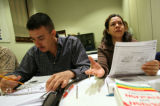 Javier Prieto (cq), left, studies a class handout while classmate Leticia Santos asks a question...