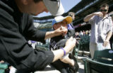 Colorado Rockies first-baseman Todd Helton autographs the shirt of 10-year-old Samuel Reed (cq) as...