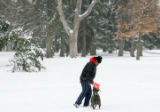 Richard Valdez (cq), of Denver, plays with his dog, Dakota on a snowy day in Cheesman Park in...