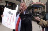 Transit Union spokesman Dave Minshall (cq) holds up 15 cents during a press conference at 16th and...