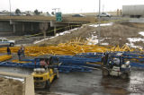 Workers clean up commercial steel shelving that spilled on the north bound on ramp to I-25 from...