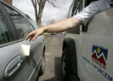 A parking enforcement agent places a ticket on a vehicle in the Wash Park neighborhood, parked in...