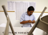 Paulo Quispe Huaracha (cq) seals his ballot in private behind a blockade of folding chairs and a...