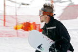 Joshua Morrison (cq), 21, of Aurora walks back up the hill with his snowboard while practicing for...