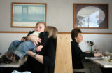 Isaiah Garcia, 1, is hoisted into a booth by his aunt, Millie White, cq, during lunch at the...