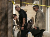 Denver Police and investigators examine bullet holes in a fence after a drive by shooting from...