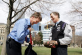 Denver Mayor John Hickenlooper, left, takes his tie off before a game of catch with Colorado...