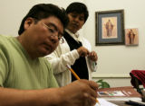 Sister Patricia Copado (cq), right, eyes the work of her student Ramiro Osorio Flores during an...