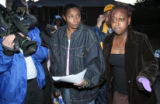 De De Davis (cq) (center) holds a police warrant to search her home as her second cousin...