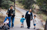 COPY PHOTOGRAPH: Won-Kee Min , left pushes his daughter Elizabeth while Mun Song, CQ, 32, walks...