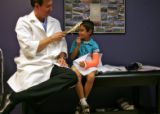 Richard G. May, MD, left,  a Colorado Orthopedic Surgery Specialist jokes around with child...