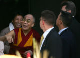 Flanked by security, the Dalai Lama smiles and waves to supporters as he walks into the Newman...