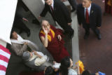 The Dali Lama, under very heavy security, arrives from his car to the center and waves at...