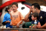 (7/15/2004 Denver) Denver Police Officer Jim Lopez tells  Evan Sanchez, 5, with brother Mikey...