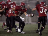 Fairview quarterback T.C. McCartney,left, hands the ball off to running back Marshall Wollum,...