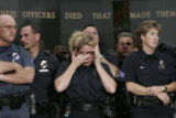 Aurora Officer Lana Jack (cq) wipes her eyes while waiting for press conference to start at the...