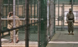 XBL103 - In this photo, reviewed by a US Department of Defense official, a detainee, left, walks...