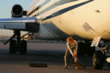 Andrea Warfield, cq, an employee for Frontier Airlines, pulls choks from the tires of a Champion...
