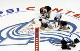 A crew of Pepsi Center employees from the mailroom to security guards paint the graphics on the...