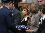 DLM00140   Lynne Schuster, center, is presented with a flag during the burial of her brother Maj....