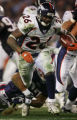 The Denver Broncos Tatum Bell burst through the the New England Patriots line during the second...