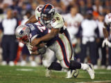 The Denver Broncos' Ian Gold (#52, LB) tackles the New England Patriots' Kevin Faulk (#33, RB)...