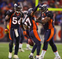 The Denver Broncos teammates Al Wilson (#56, LB) and Demetrin Veal (#97, DT) celebrate with...
