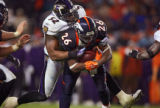 The Denver Broncos' Tatum Bell (#26, RB) carries the Baltimore Ravens' Ray Lewis (#52, LB) on his...