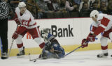 Colorado Avalanche #29 Matt Murley slides after the puck with Detroit Red Wings #64 Matt Hussey,...