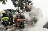 Denver firefighters punch a hole in the roof of a house fire at 9 South Elati Street Tuesday...