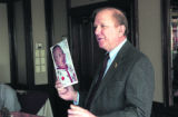 (THORNTON, Colo., October 12, 2004) Norm Olsen speaks and holds up a photo of his grandson Seth...