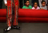 MJM302  Henry Higinio (cq, left, performs for children as Elias Gonzalez, 11, watches with sister,...