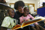 DLM03223   Commander Tracie Keesee, center, with the Denver Police reads to first-graders Viola...