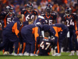 The Denver Broncos' defense gathers as trainers attend to John Lynch (#47, S) after Lynch injured...