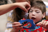 MJM107 Simon Nelson, 6, of Fort Collins, Co. does crafts as he is held by his mother, Cheryl...