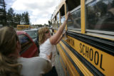Renee Corbino, CQ, reaches for her daughter Summer Corbino, 15, as a school bus full of evacuated...
